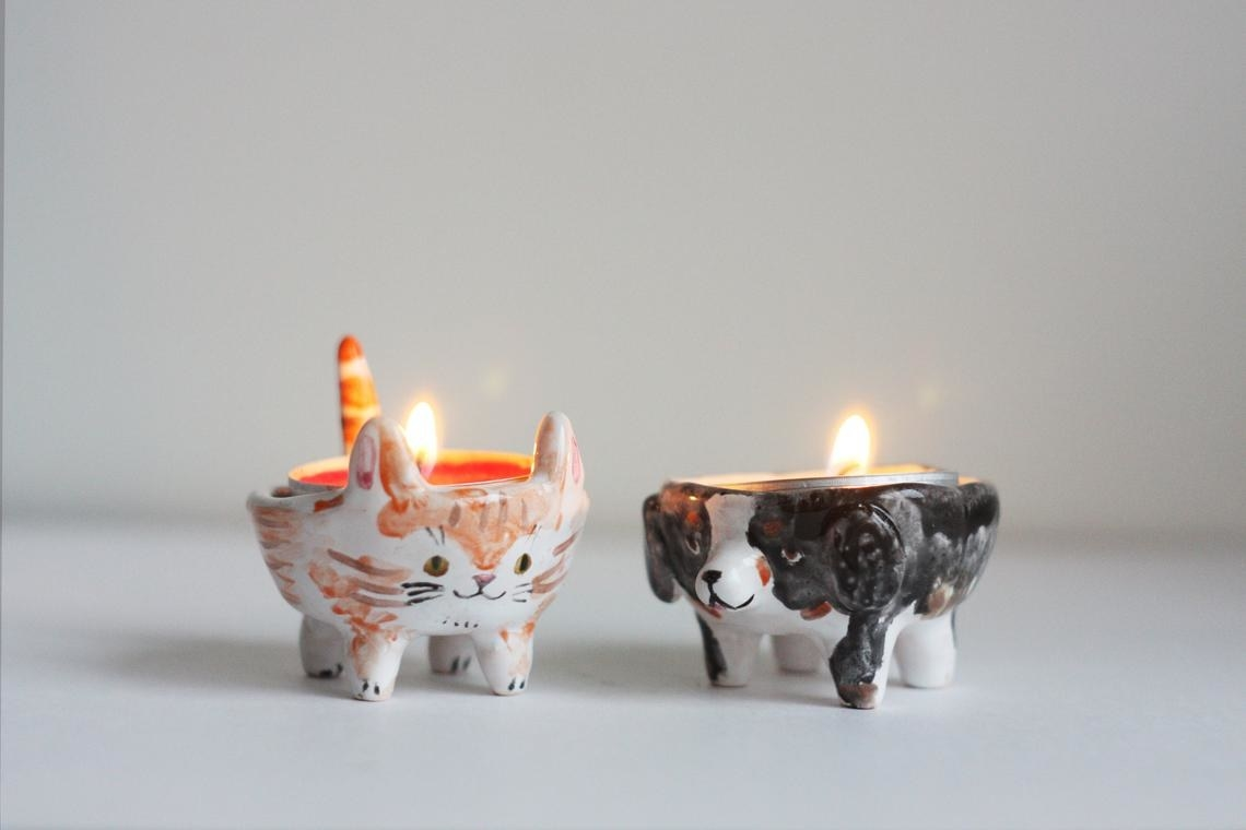 clay cat and dog with candles on their backs