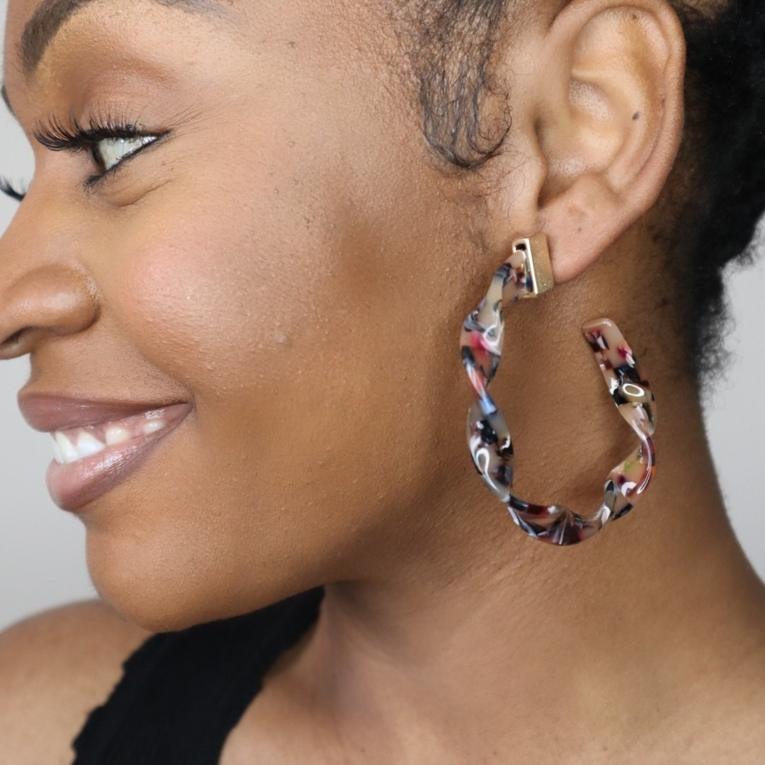model wearing colorful acrylic hoops in a twisted pattern