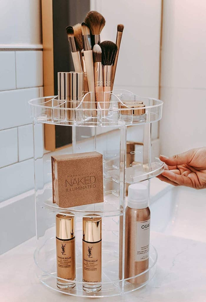 A person pulling out one of the shelving trays on the rotating caddy that is holding various beauty products