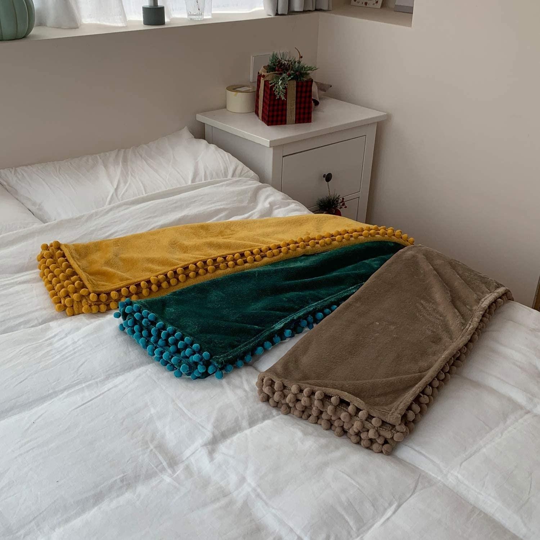 Three fleece blankets with pom pom edges