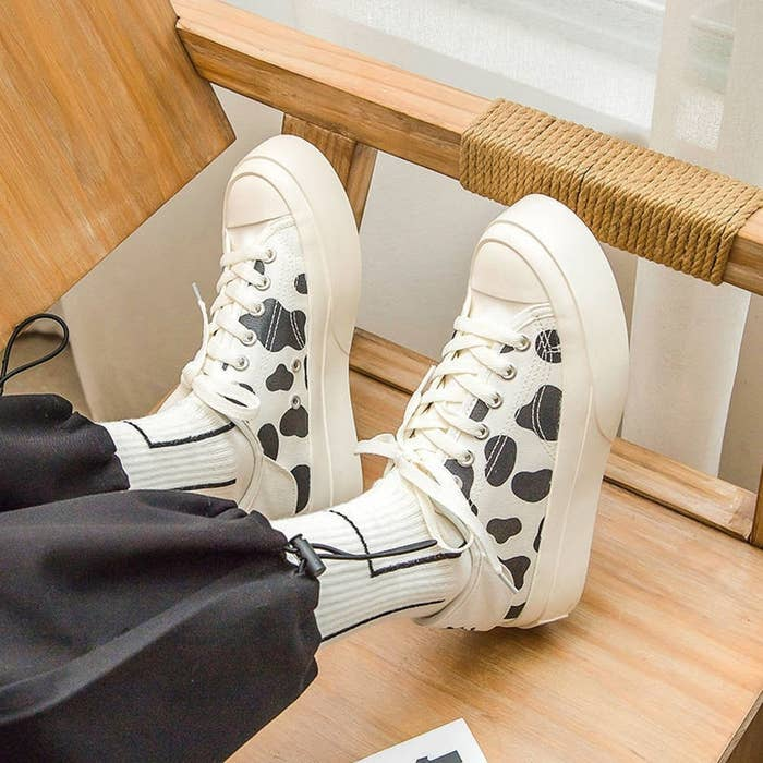 Low top with sneakers with thick soles, canvas cow-print tops, and white laces. They're paired with tall socks.