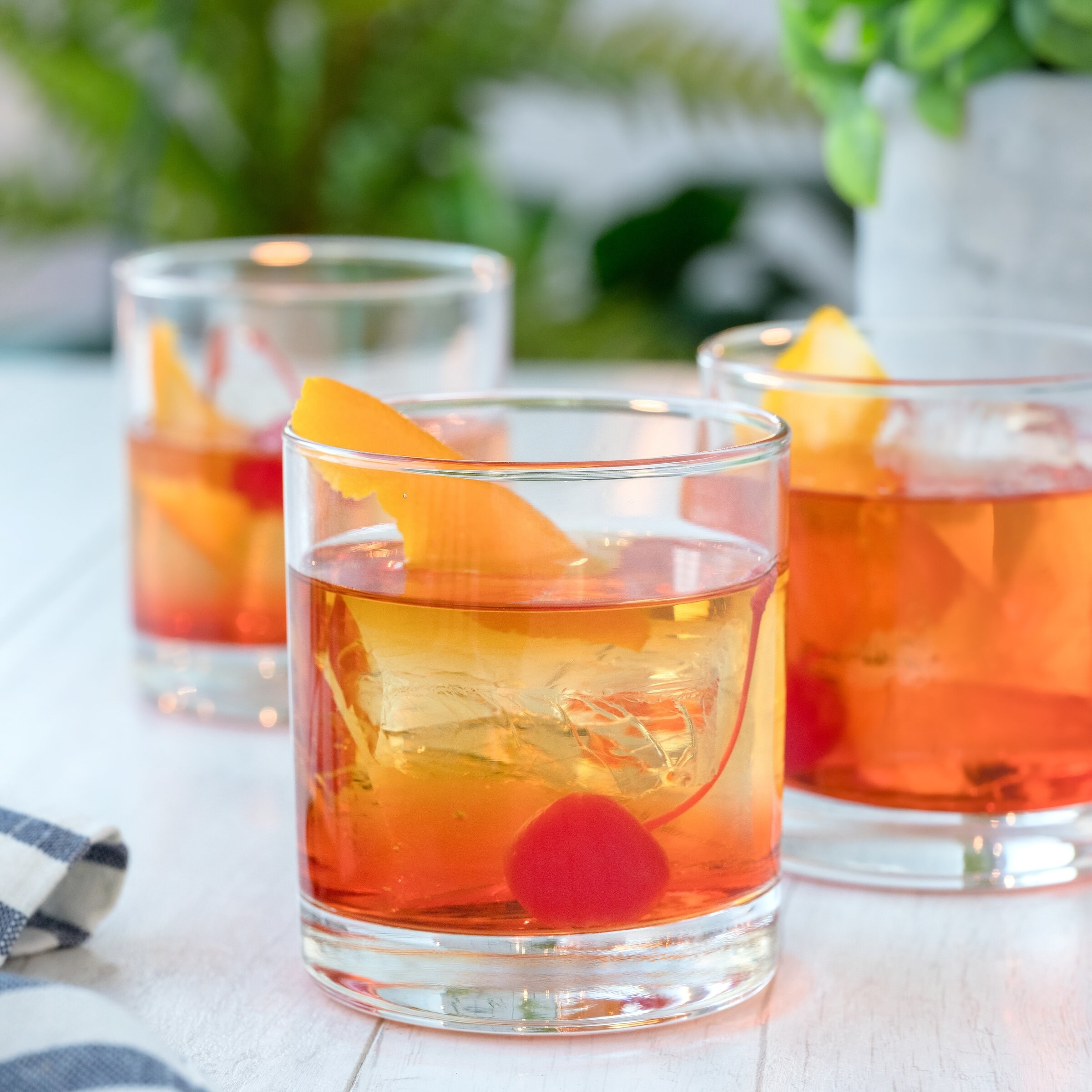 The glasses with fancy orange cocktails in them on an outdoor table