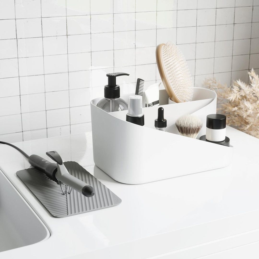 A countertop organizer with separate compartments and a detachable silicone mat on a bathroom counter