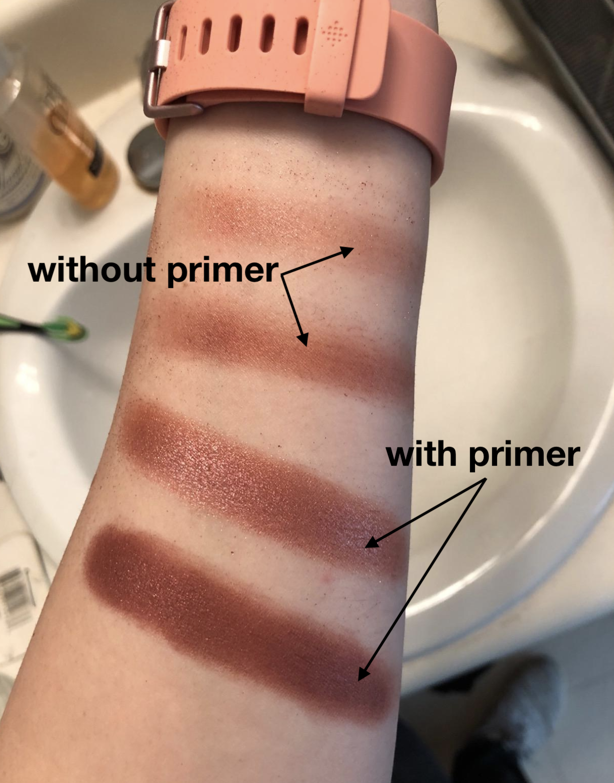 reviewer swatching eyeshadow on arm with and without primer. the shadows without were less vibrant, and the ones with were much more bold and pigmented.