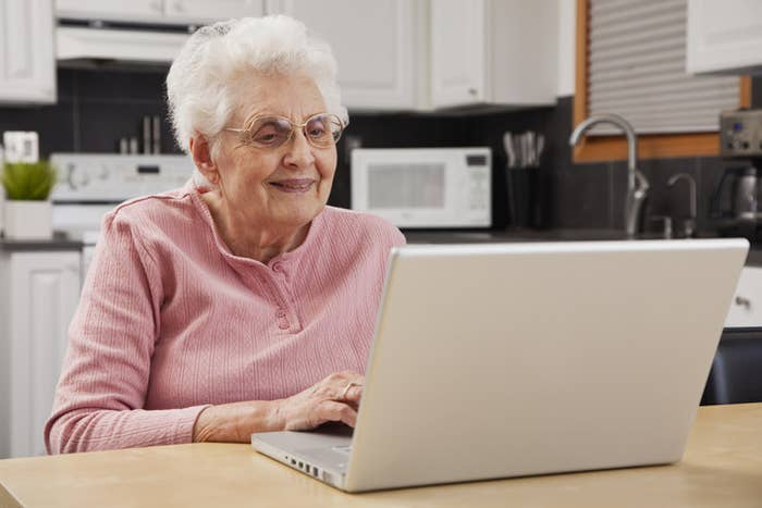 An old woman smiling at her laptop screen