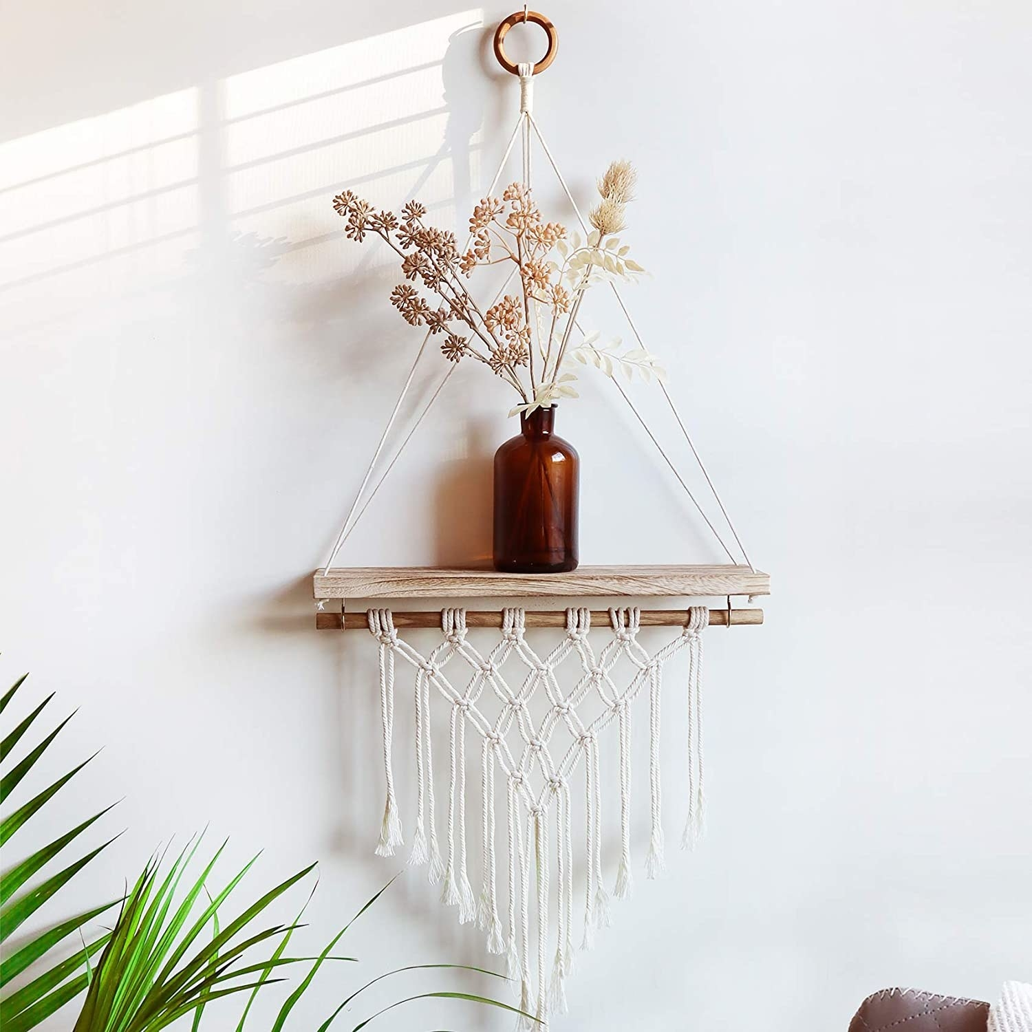 A hanging shelf decorated with macrame with a vase of flowers sitting on it
