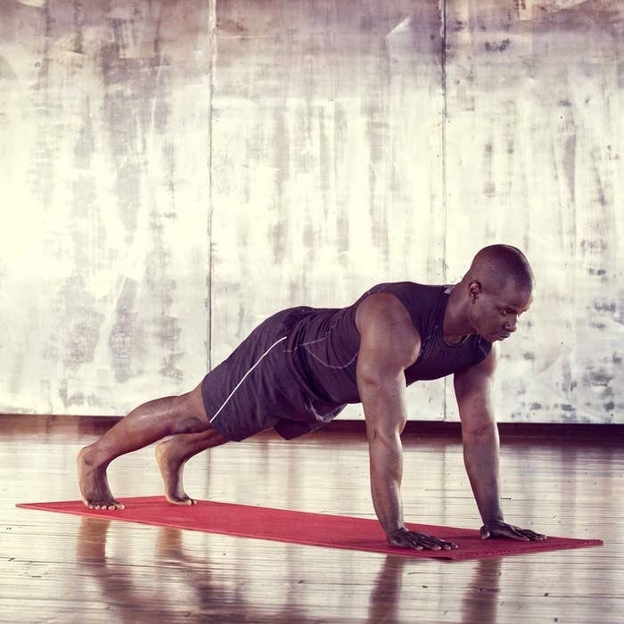 model in plank position on red yoga mat in studio