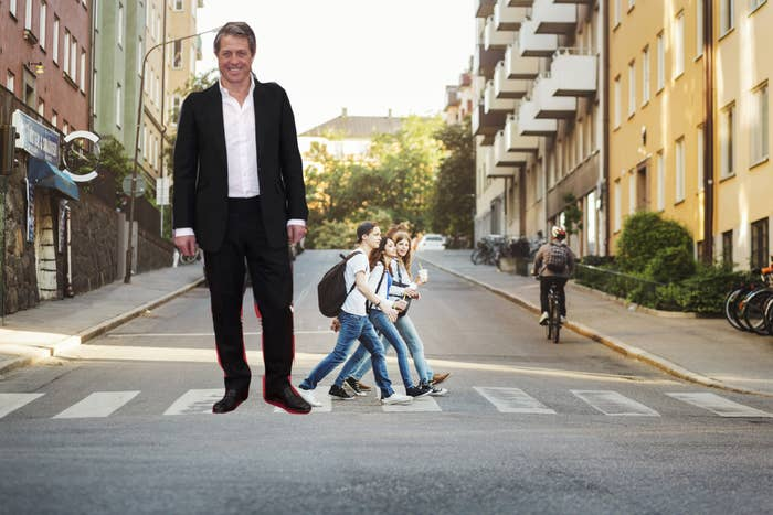 Hugh Grant made to look like a giant standing next to average-size people who are crossing a street