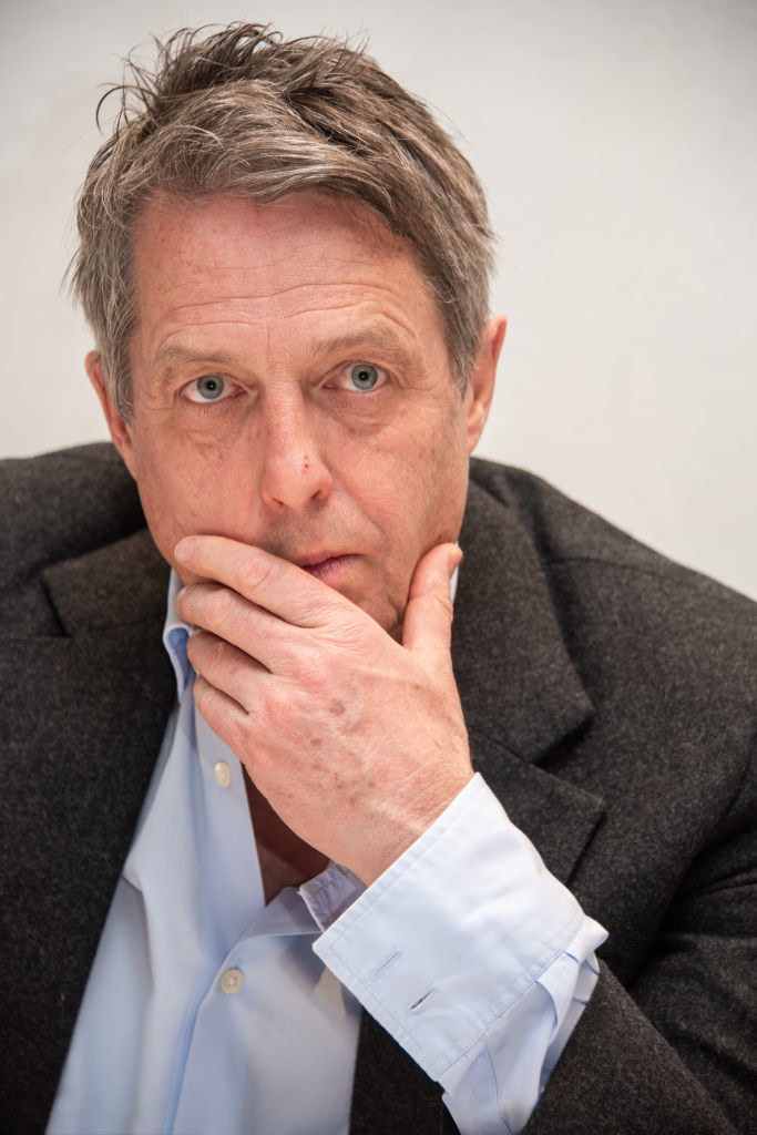 Hugh with his hand on his jaw as he contemplates something