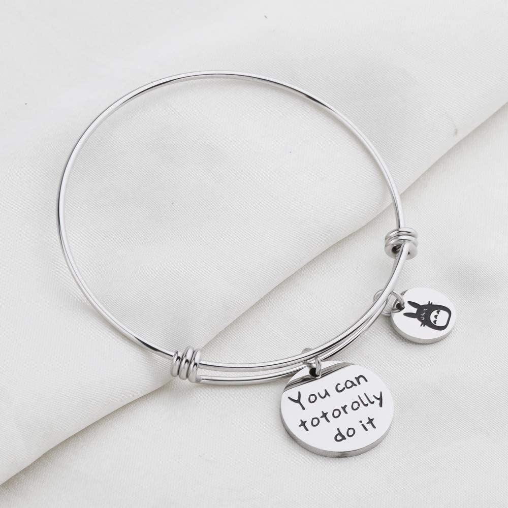 "silver tone bangle with two round charms, a small one with an image of Totoro and a larger one that reads ""you can totorolly do it"""