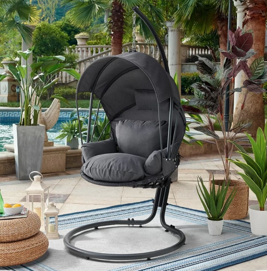 A grey, swinging lounge chair with a built-in canopy displayed on a patio