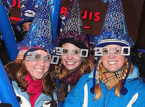 People celebrating New Year's Eve by wearing glasses shaped like the numbers 2010