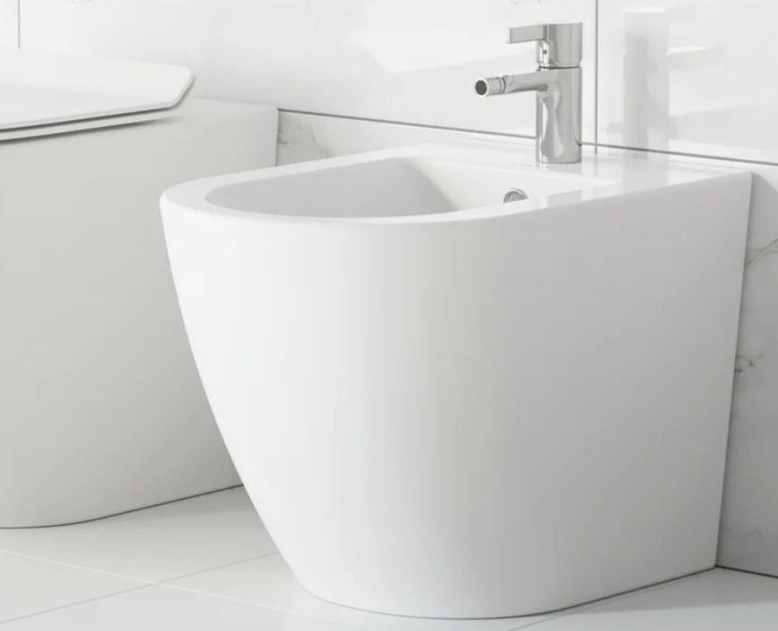 A white, floor mounted bidet displayed next to a toilet