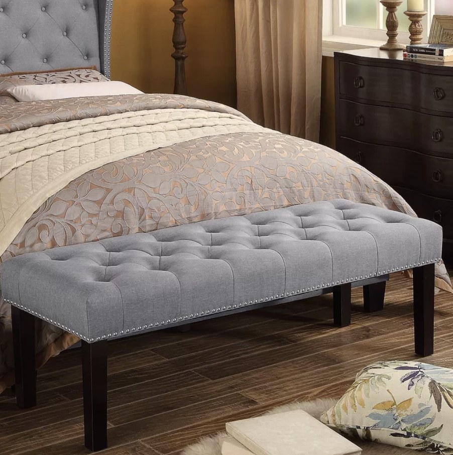 A grey, tufted upholstered bench displayed at the foot of a bed