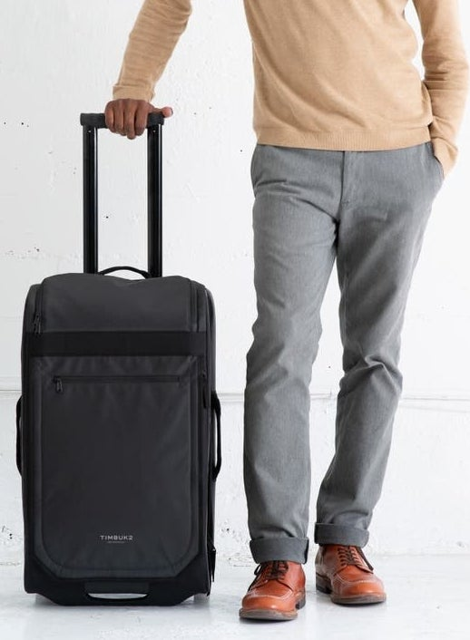 A model stands next to the suitcase, which comes up to mid-thigh, and the extended handle goes to their waist