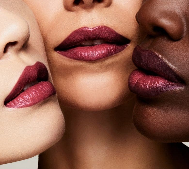 Three models with different skin tones wear the lipstick in Adora
