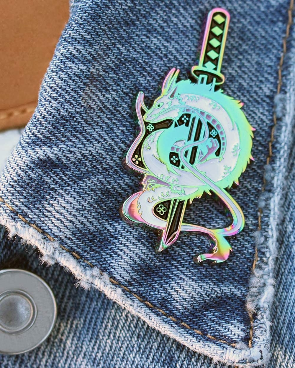 rainbow holographic enamel pin of Haku in dragon form wrapped around a sword, attached to the collar of a denim jacket