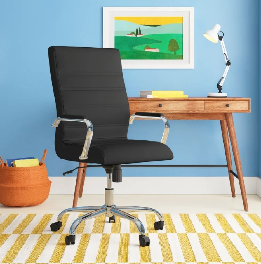 A black, ergonomic office chair with a swivel seat and center tilt feature that locks in place