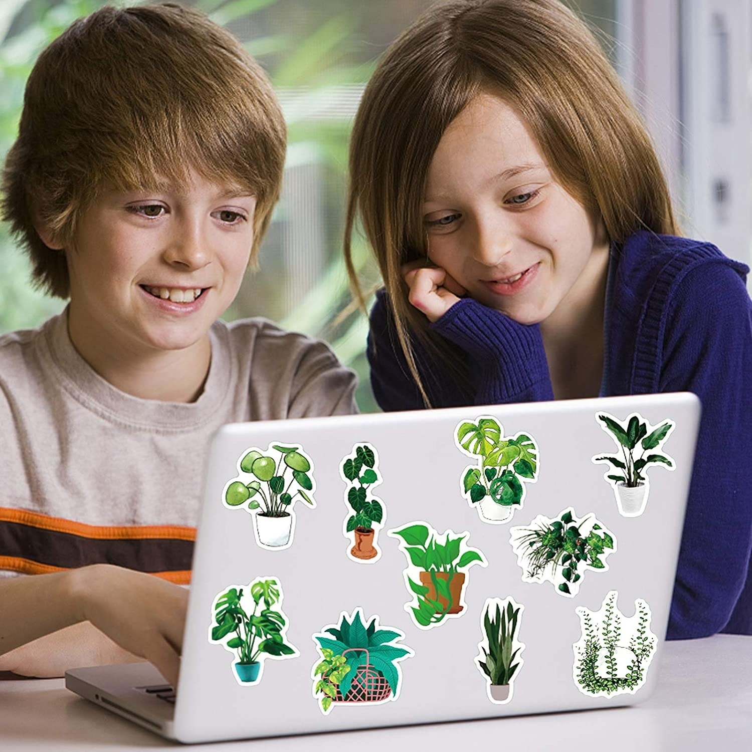 two kids on a laptop that is covered in the stickers