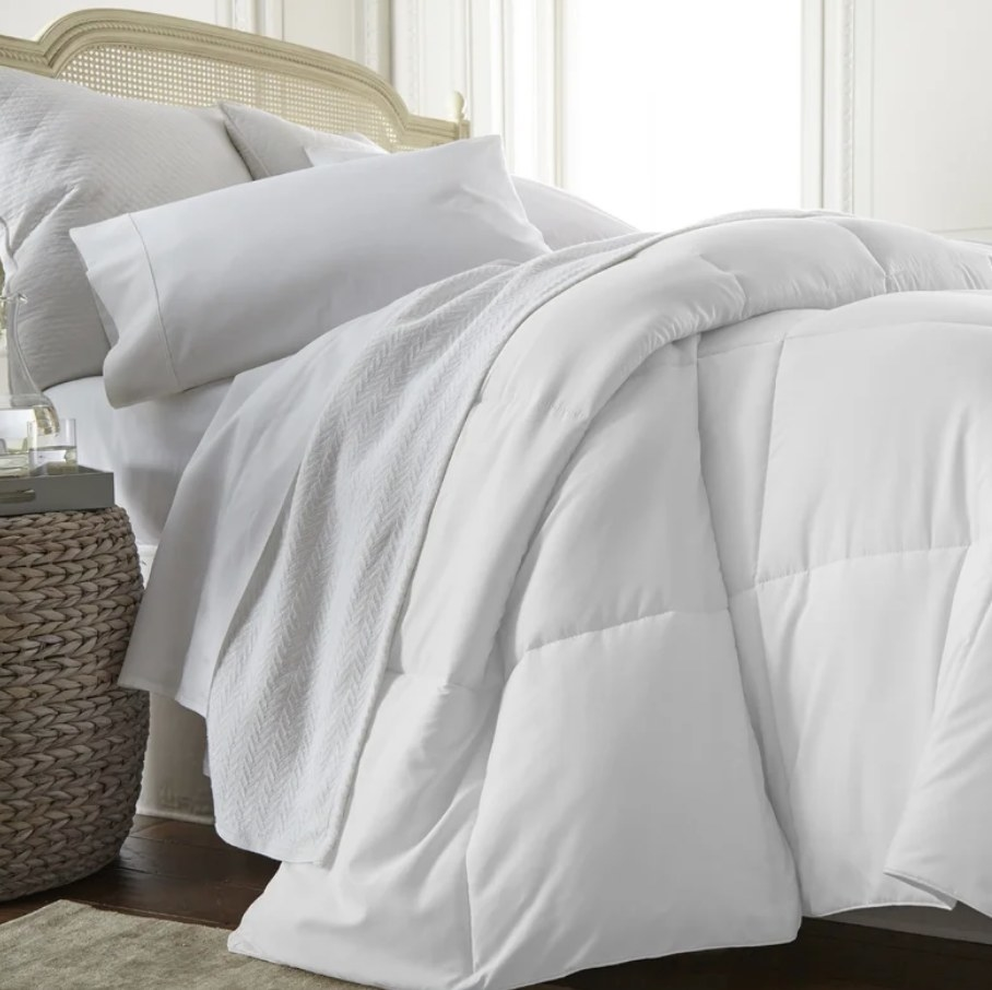 A white, microfiber down comforter draped over a bed