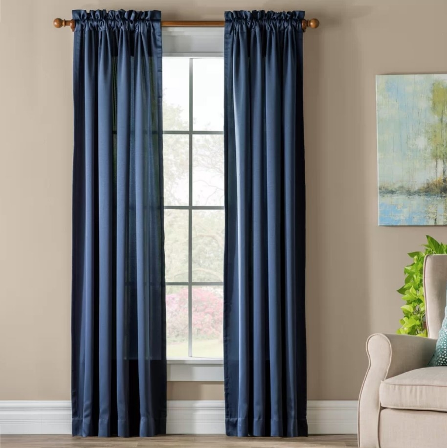 A navy, room-darkening curtain hung up on a rod pocket header displayed over a window inside a living room