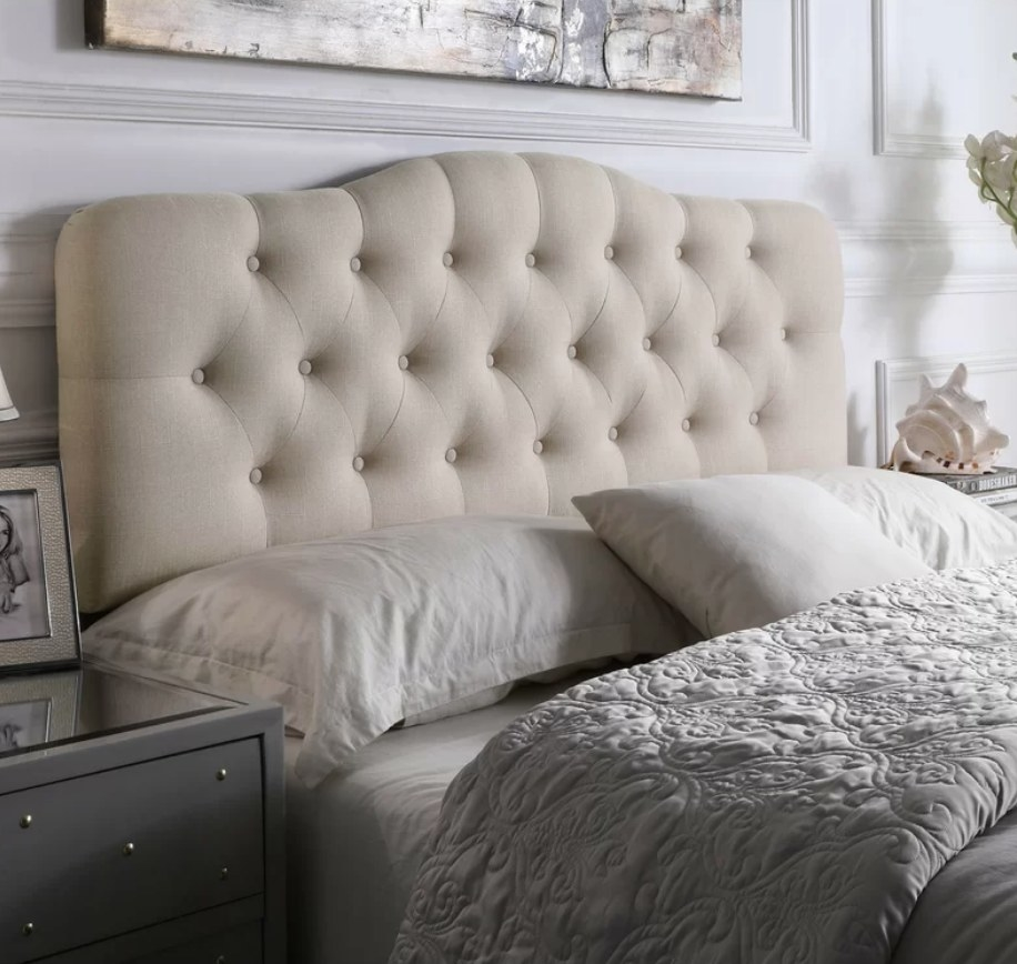 A light beige upholstered panel headboard displayed in a bedroom