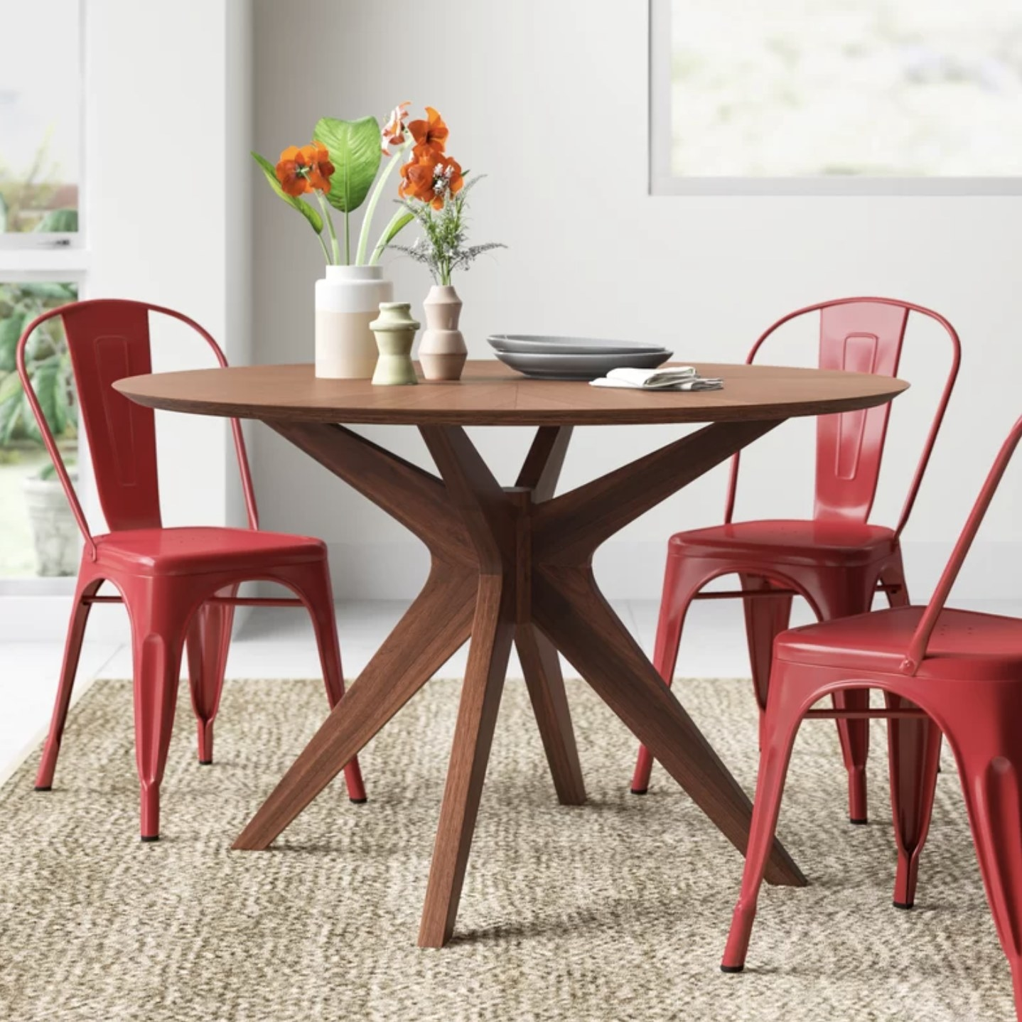 The dining room table in a wood color with red chairs surrounding it
