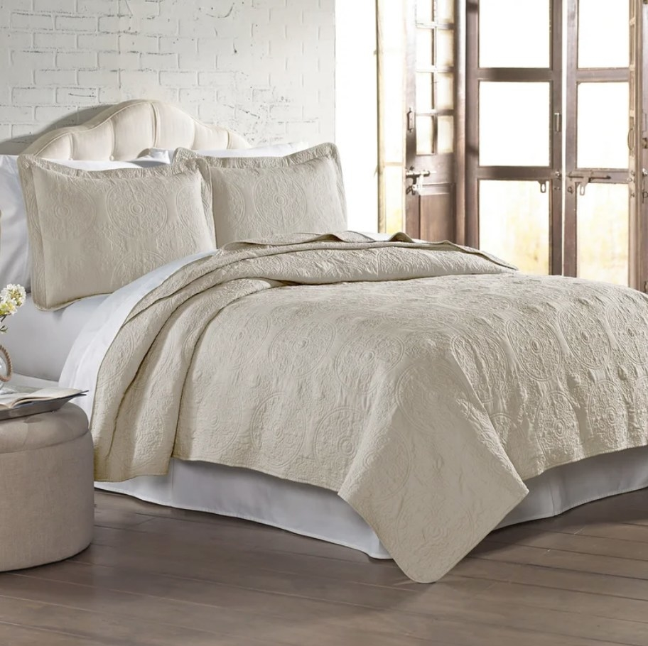 A sand beige quilt with two matching pillows displayed on a queen sized bed