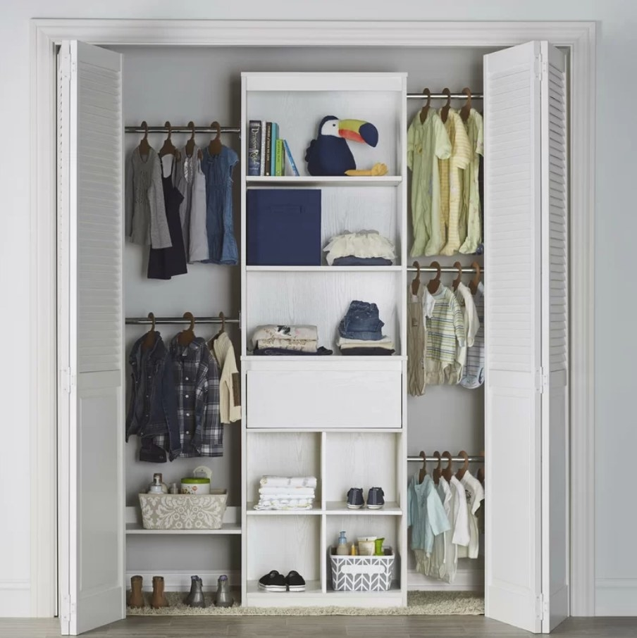 A white, wall-mounted closet system with eight shelves, one drawer, and five hanging rods filled with a variety of clothing and shoes