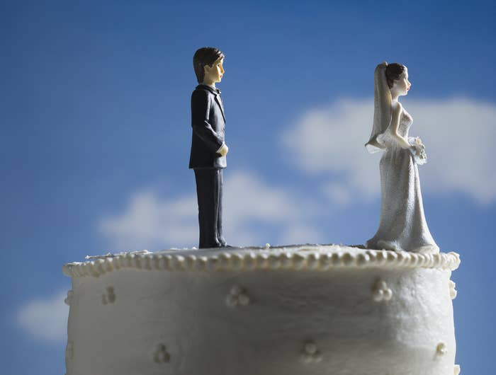 Photo of wedding cake with the bride topper walking away
