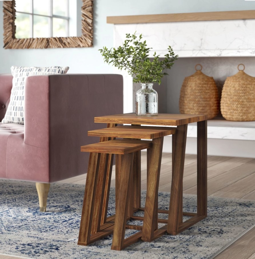A 3-piece wooden nesting tables displayed next to a couch in a living room