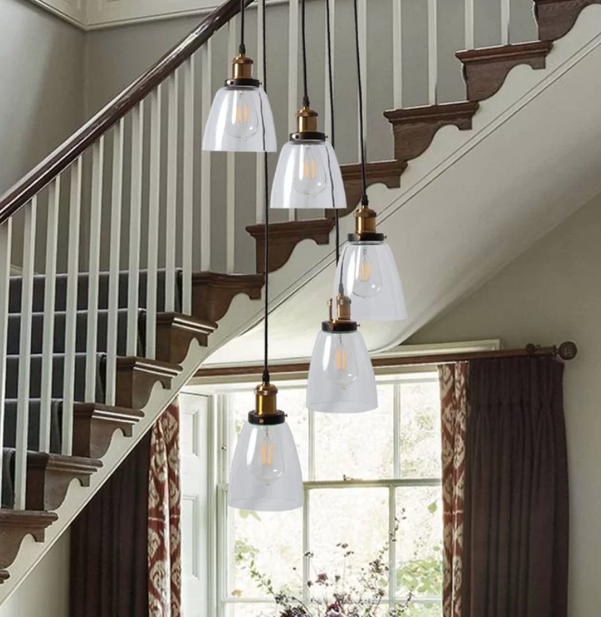 A 5-light, suspending pendant that can be adjusted to a desired height featured in an entryway