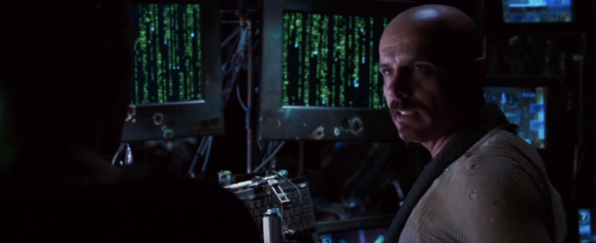 Neo looking at computers with code on them