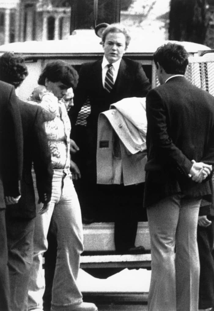 Arne C. Johnson, with coat over arm, steps from a police van on arrival at court in Danbury, CT for the opening day of his trial o