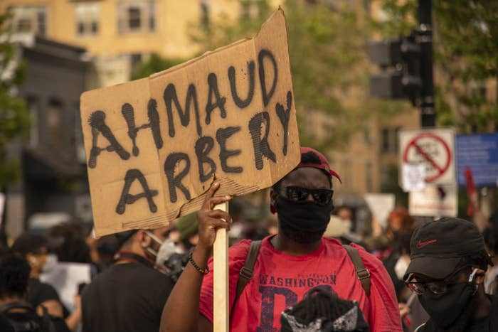 A man at a demonstration holds up a cardboard sign with Ahmaud Arbery's name
