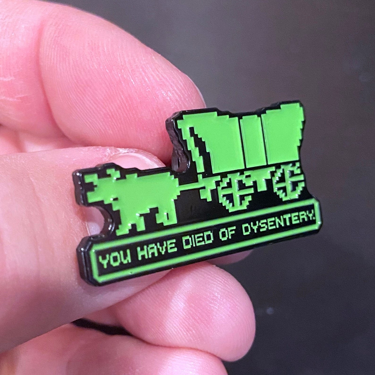 """a green pin shaped like a horse and carriage that says """"you have died of dysentery"""" under it"""
