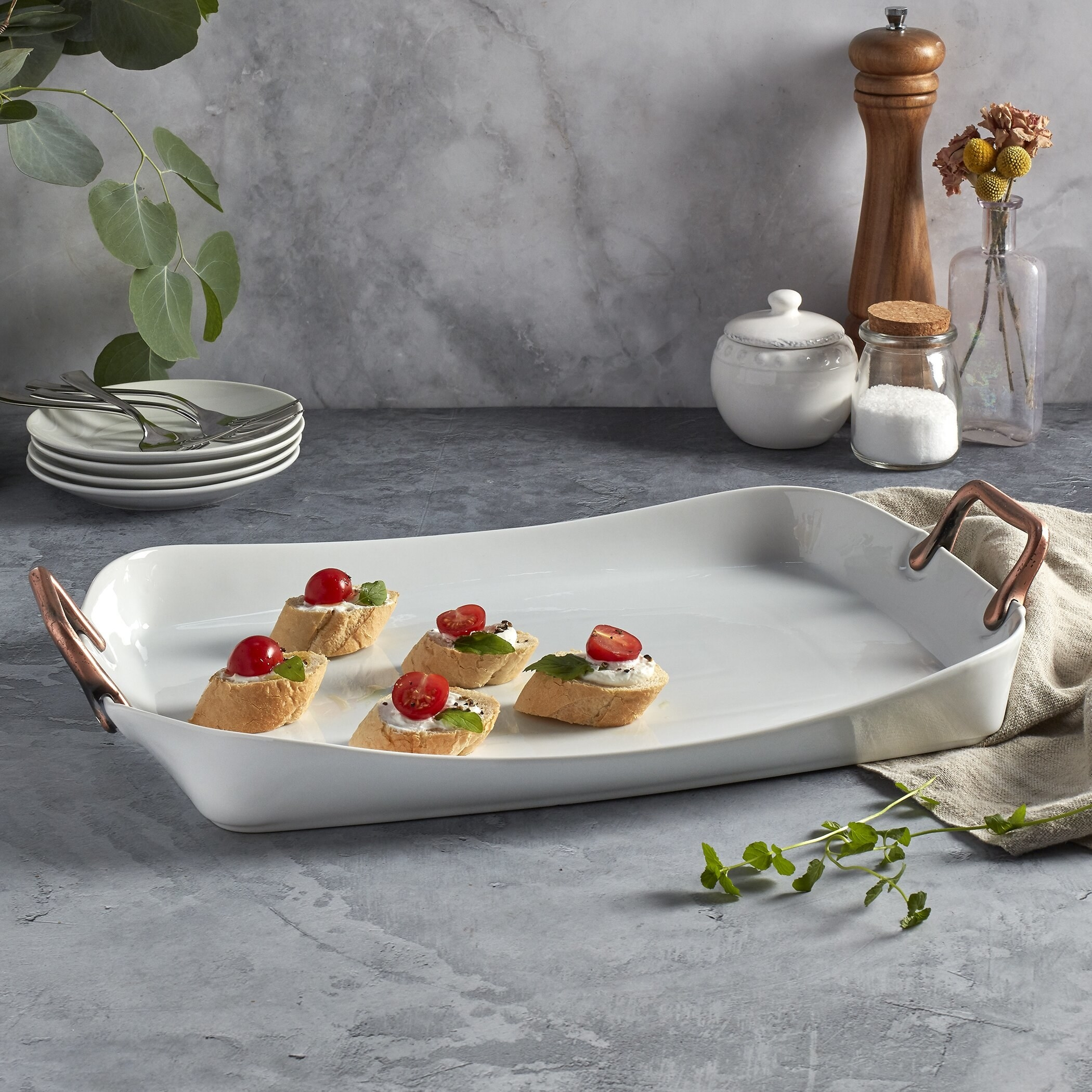 The white tray with copper handles with toast appetizers on display