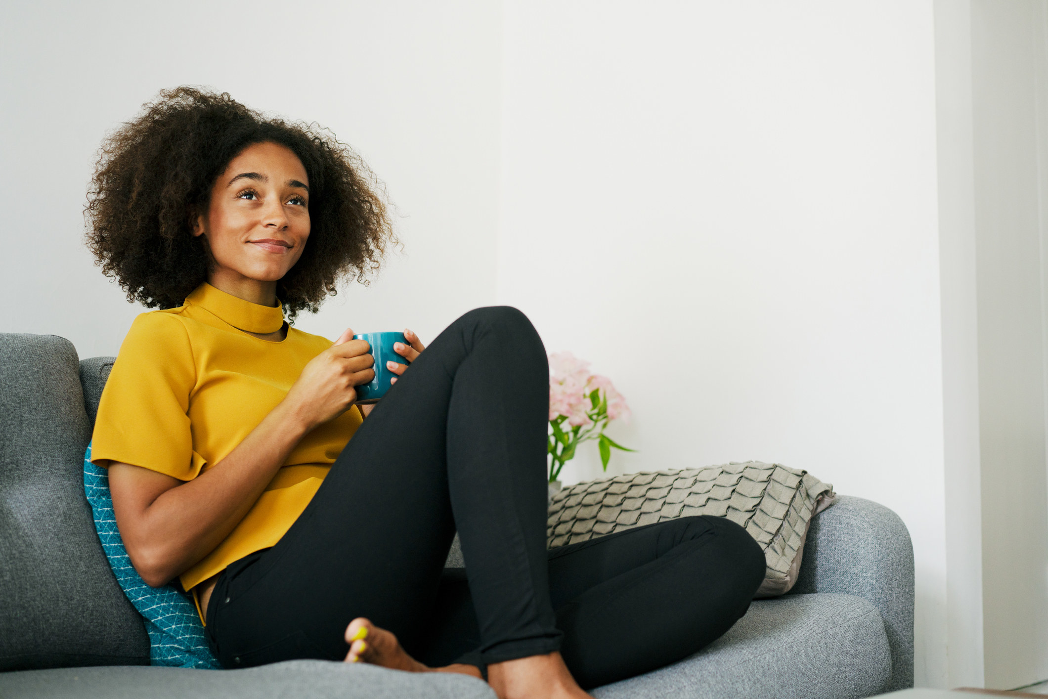 Woman sitting on her couch drinking coffee