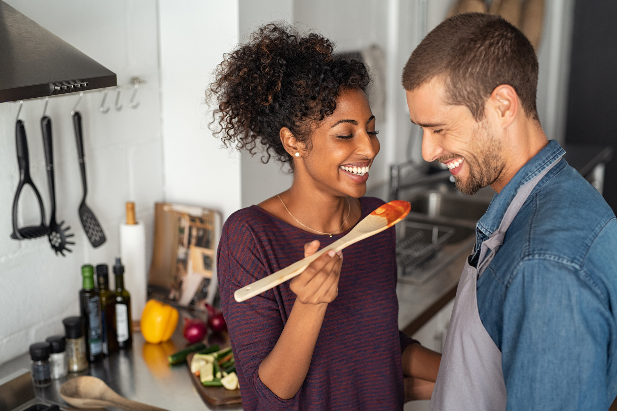 Girlfriend having her boyfriend try some pasta sauce from a wooden spoon