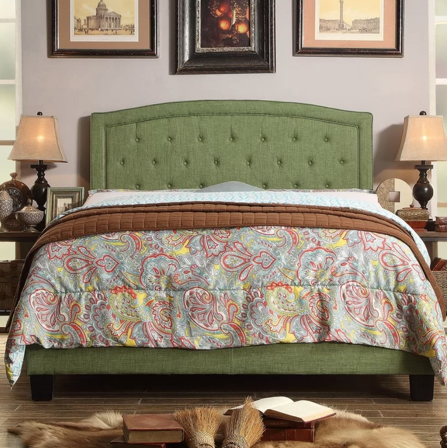 A green, tufted upholstered low profile bed paired with a colorful duvet, displayed in a bedroom