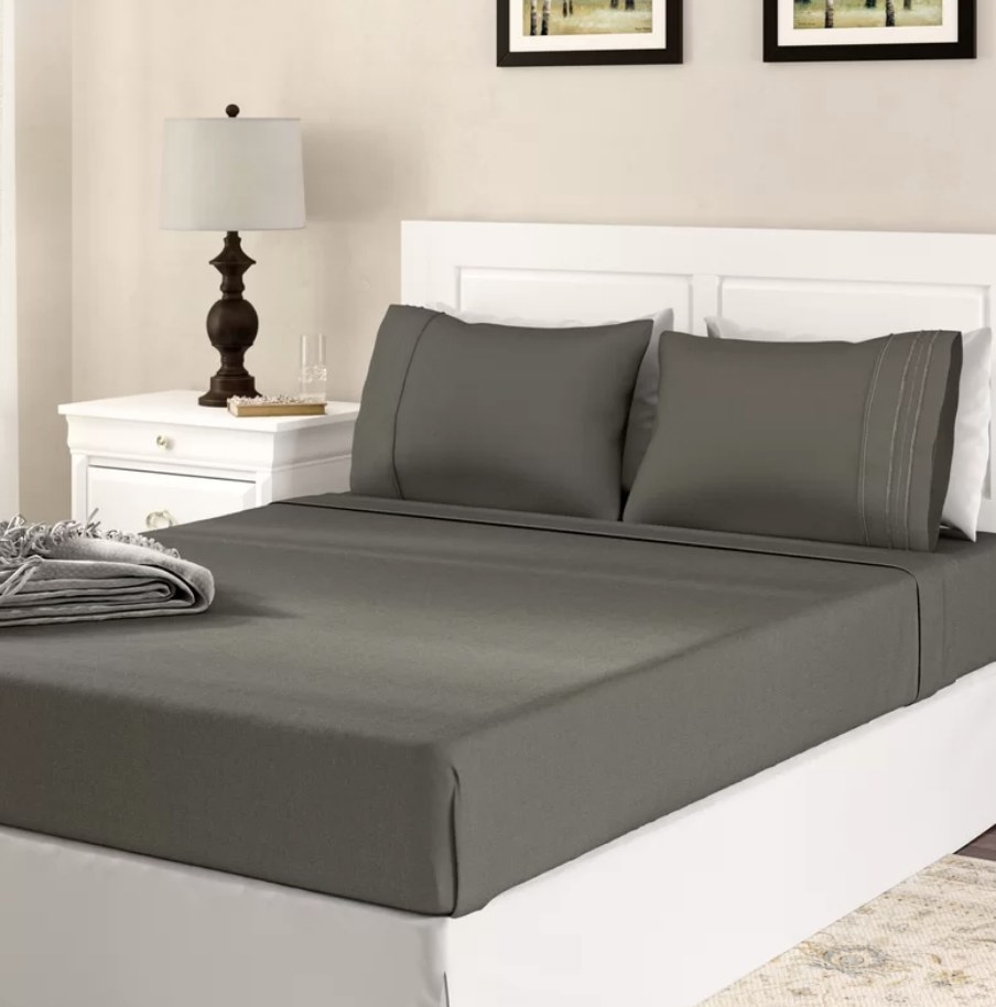 A dark gray, 1800 thread count bamboo blended sheet set on a bed