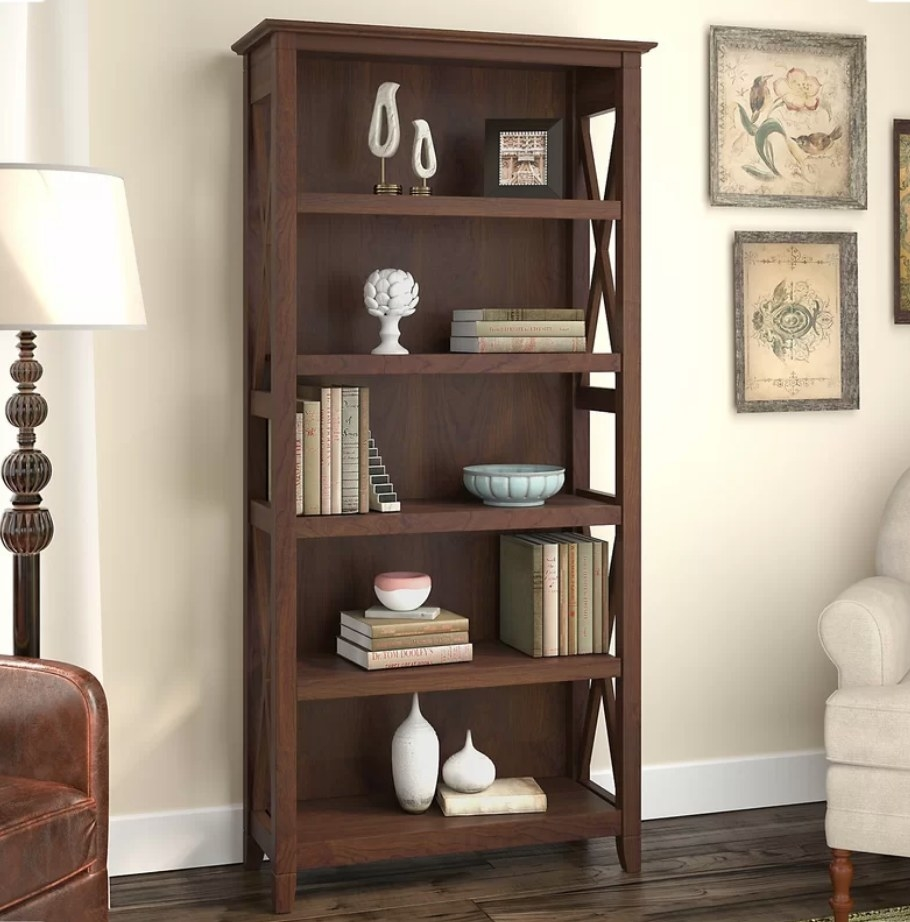 A bing cherry, wooden, five-shelf bookcase filled with decor items such as books, vases, and picture frames