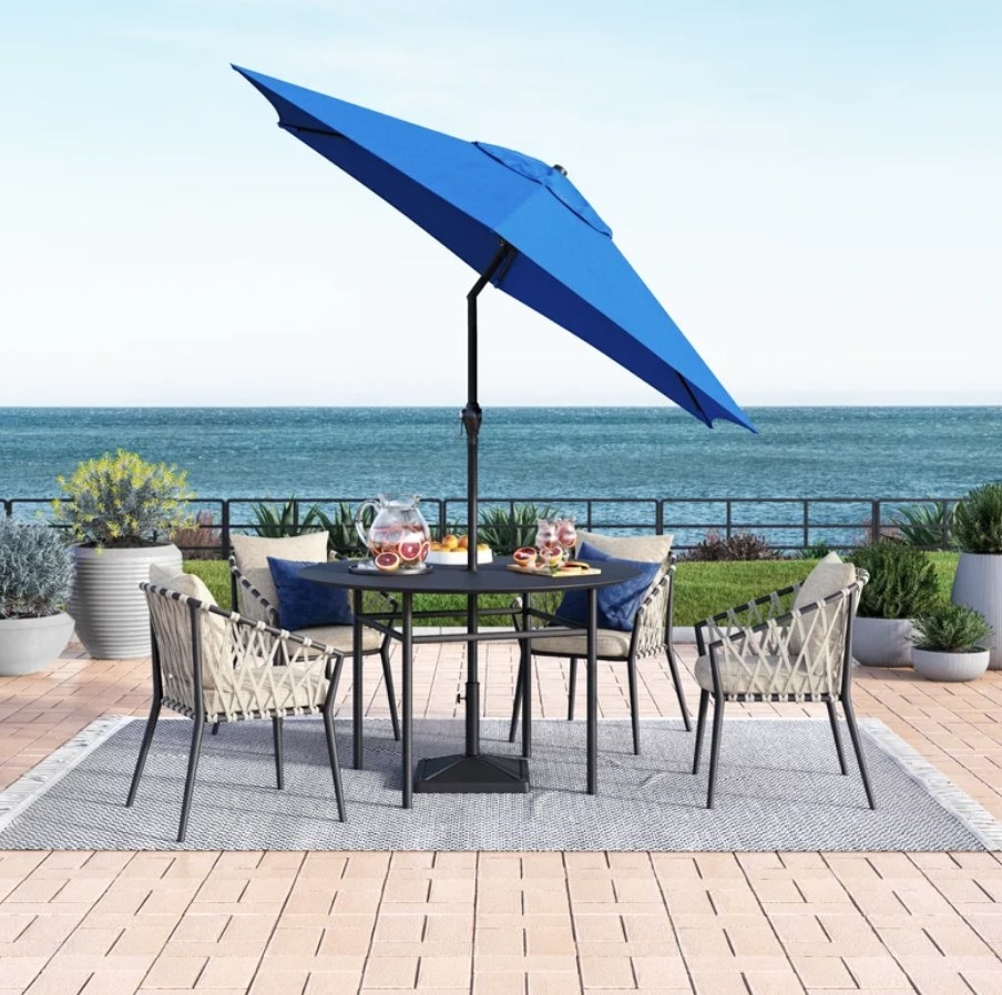 A blue, 9-foot outdoor umbrella with a tilt feature and crank lift displayed over an outdoor dining set