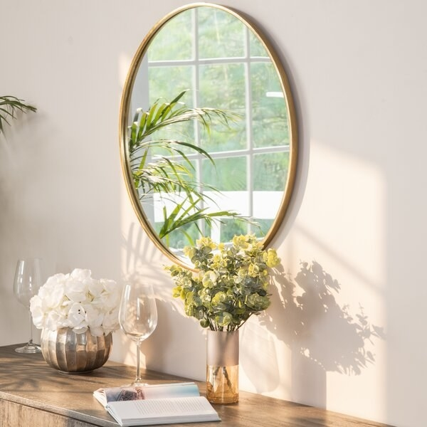 The mirror in gold, above a console table
