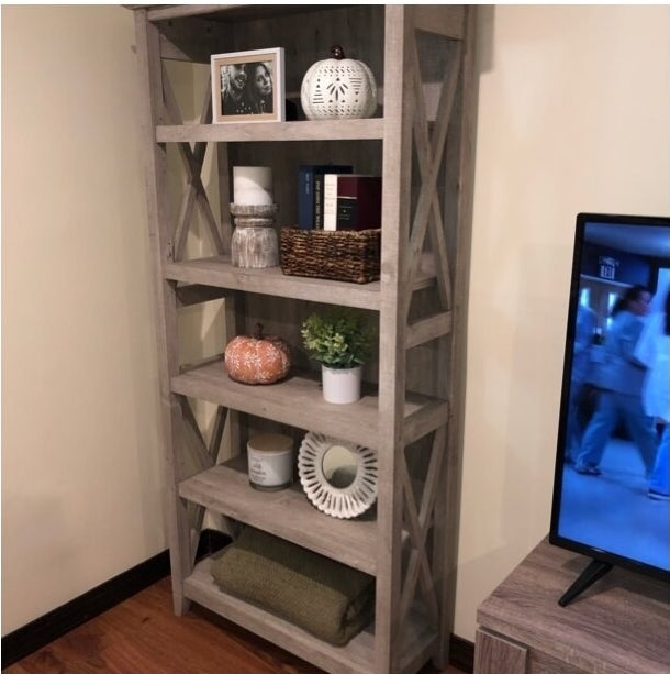 """The bookcase, which has open sides with """"X"""" wooden framing"""