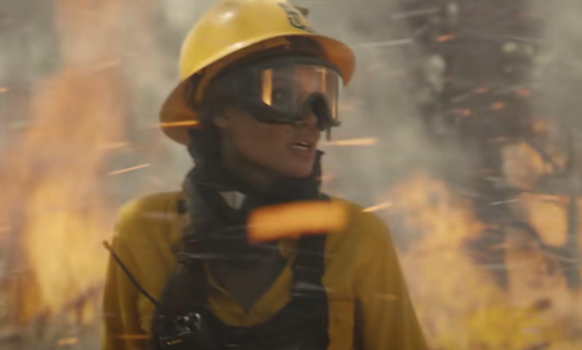 Angelina wears firefighter gear in the forest