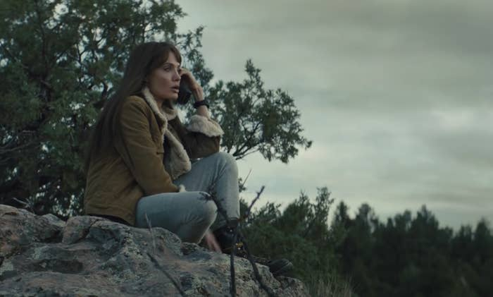 Angelina talks on the phone while sitting on a rock in the forest