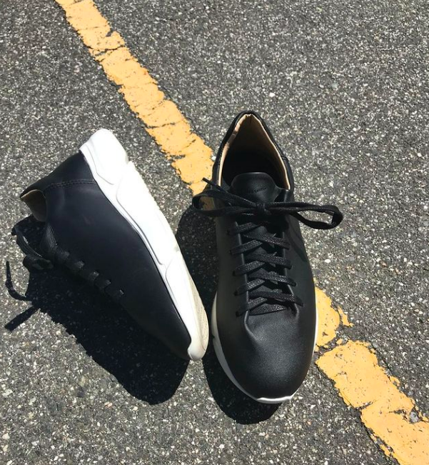 Matte black sneakers with large white shoes and black laces