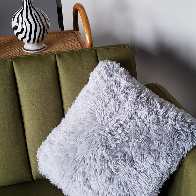 Reviewer's photo of the fuzzy pillow in grey, on their couch