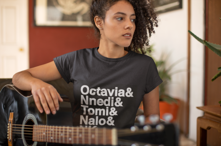 """Young Black woman wears a black tee-shirt with large text reading """"Octavia & Nnedi & Tomi & Nalo & NK"""", with her arm resting on a guitar."""